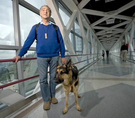 Urban Miyares seen walking down hallway with seeing eye dog by his side